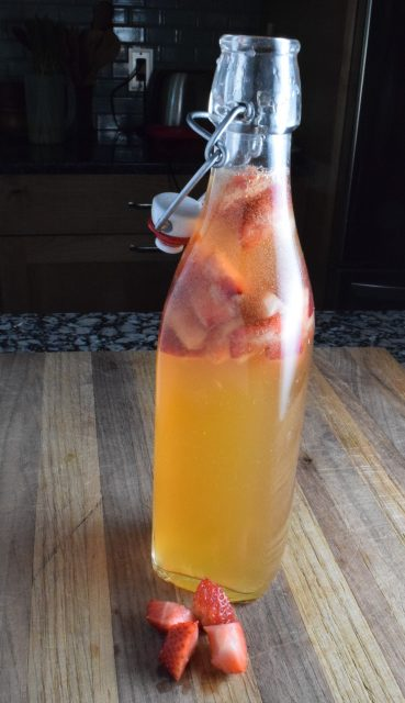 Strawberry Lemonade Kombucha in bottle on cutting board